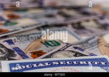 Social Security Card und ein Bett, das Geld für die hohen Kosten des Lebens auf einem festen Einkommen ICH - Stockfoto