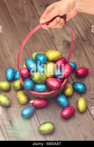 Hand herauf ein strohkorb mit Ostern Schokolade Eier in bunte Stanniolpapier auf einem hölzernen Tisch gewickelt - Stockfoto