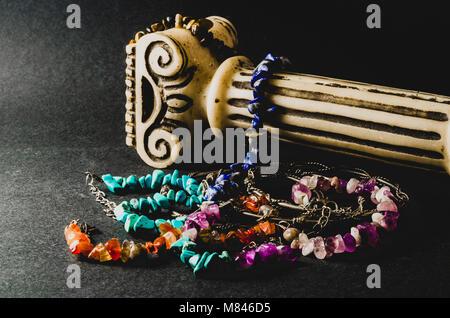 Bunte Armbänder von Natursteinen und antiken Säule auf grauem Hintergrund - Stockfoto