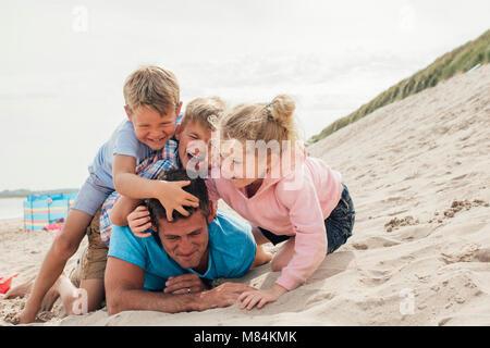 Kinder Spaß am Strand mit ihrem Vater. Er verdorrte und Kitzeln ihn. - Stockfoto
