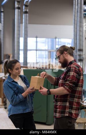 Männliche und weibliche Schreiner Prüfung ein Stück von Holzmöbeln - Stockfoto