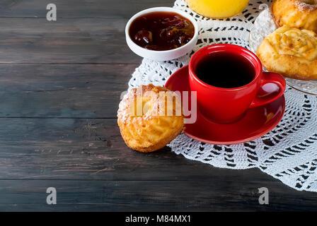 Hausgemachten Kuchen bei einer Tasse starken Kaffee, Marmelade und Orangensaft auf einem dunklen alten hölzernen Hintergrund. Kopieren Sie Platz. Stockfoto