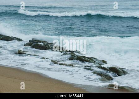 Schaumige Meerwasser fließt um Felsen nach einer Brechenden Welle - Stockfoto