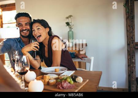 Junger Mann und Frau sitzt am Esstisch lachen während der Einnahme von selfie. Paar beim Party zu Hause. - Stockfoto