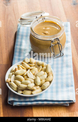 Erdnussbutter im Glas und Erdnüsse auf hölzernen Tisch. - Stockfoto