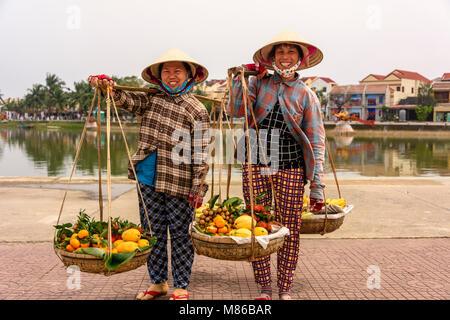 Zwei Obst Verkäufer tragen traditionelle Bambus konischen Hüten, Obst in bambuskörben von einem Pol in Hoi An, Vietnam. - Stockfoto