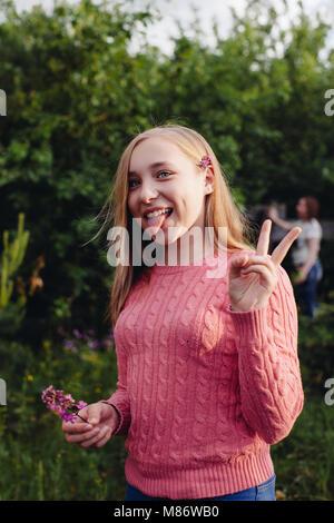 Mädchen ihre Zunge heraus und ein v-Zeichen - Stockfoto
