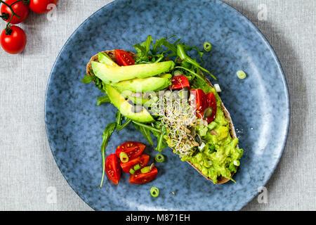 Roggen Toast mit Avocado, Tomaten und Alfalfa Sprossen - Stockfoto