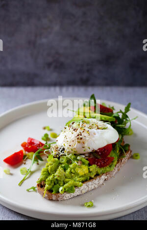 Roggen Toast mit Avocado, Tomaten, Alfalfa Sprossen und pochiertem Ei - Stockfoto