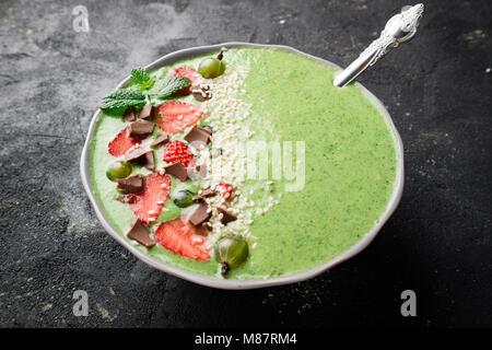 Frühstück smoothie Schüssel mit Kiwi, Spinat, Erdbeeren, Stachelbeeren, Schokolade und Sesam auf dunklen konkreten - Stockfoto
