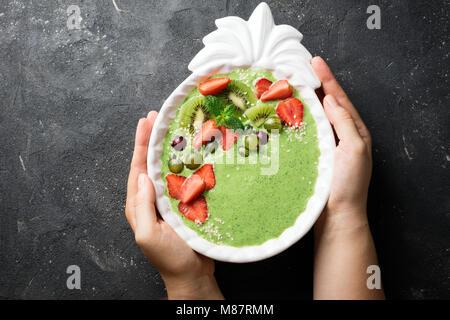 Weibliche Hände halten Smoothie Schüssel mit Kiwi, Spinat, Erdbeeren und Berry. Gesunde Ernährung Diät Konzept - Stockfoto