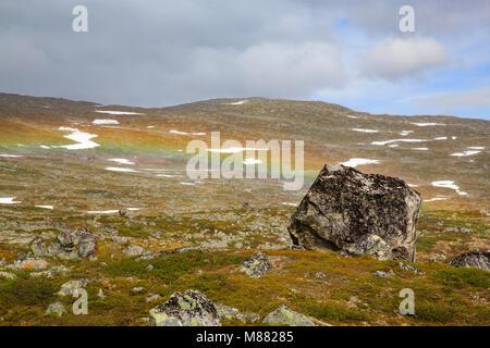 Rainbow scheinbar hinter einem kleinen Felsen im Berg Hügel zu Ende - Stockfoto