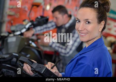 Frau Mechaniker reparieren ein Motorrad in einem Workshop