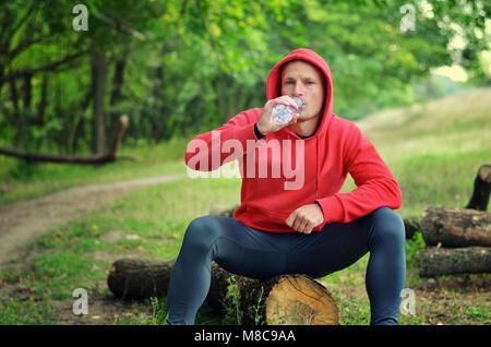 Eine junge sportliche Jogger in eine rote Jacke mit Kapuze und schwarze Leggings sitzt auf einem Baumstamm und Trinken - Stockfoto