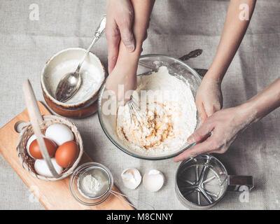 Mütter und Kinder Hände Kochen Teig für hausgemachte Cookies. Wir kochen in der Küche zusammen mit Kindern. Glückliche - Stockfoto