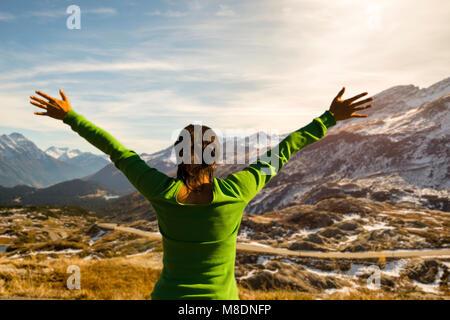 Frau mit ausgestreckten Armen über Mountain Road mit Blick in Graubünden, Schweiz - Stockfoto