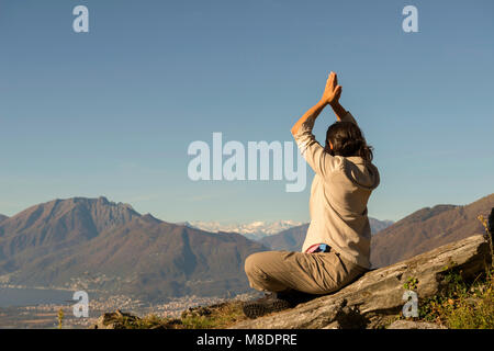 Frau Yoga auf der Spitze des Berges in einem sonnigen Tag im Tessin, Schweiz - Stockfoto