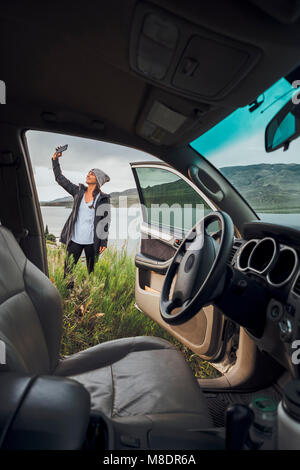 Junge Frau stand neben Dillon Reservoir, Smartphone, Blick durch die geparkten Auto, Silverthorne, Colorado, USA - Stockfoto