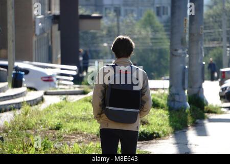 Ein Junge trägt eine Kappe mit einem Rucksack zu Fuß durch die Stadt - Stockfoto