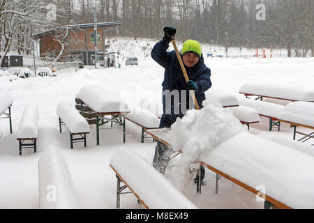 Schierke, Deutschland. 17 Mär, 2018. Hasselfelde: Ein Mitarbeiter eines Restaurant löscht Schnee von Tabellen mit - Stockfoto
