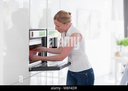 Frau mit Ofen in der Küche - Stockfoto