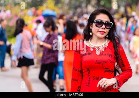 Ein Vietnam Frau im roten Kleid sagen, mehrfach aigon', und ein Paar von Gucci Sonnenbrillen, Ho Chi Minh City, - Stockfoto
