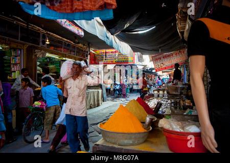 Eine ältere Inder ist Wandern und Pflege vollen Beutel der Waren auf seine Schulter, gehen durch besetzt Clock Tower - Stockfoto