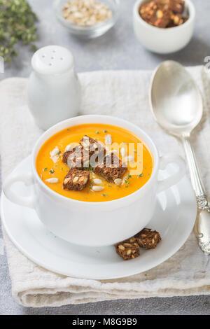 Köstliche diätetische Karotte oder Kürbissuppe mit Croutons, Sonnenblumenkerne und Thymian in eine weiße Platte. - Stockfoto