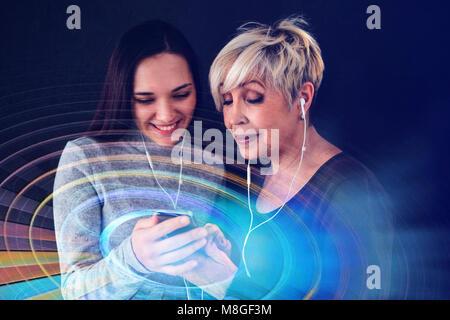 Eine ältere Frau und ein junges Mädchen hören Sie Musik zusammen. Die Kommunikation zwischen Menschen unterschiedlicher - Stockfoto