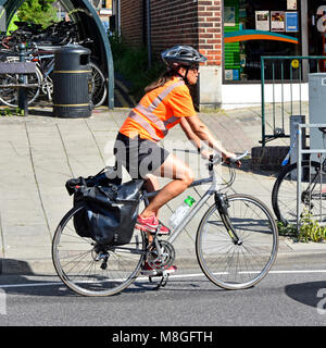 Junge Frau Radfahren und Ausübung von Fahrrad Fahrrad Helm tragen, hart, Hut & High vis Jacke entlang der städtischen - Stockfoto