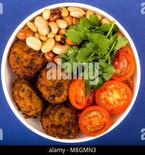 Schüssel vegetarische oder vegane Falafel Koriander Bohnen und Tomaten Buddha Schüssel gegen einen dunkelblauen - Stockfoto