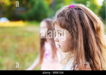 Wunderschöne kleine Mädchen mit langen lockigen Haar, auf der Suche nach Sommer Tag besorgt. Für text - Stockfoto
