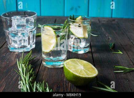 Alkoholische Getränk - Gin Tonic Cocktail - mit Kalk, Rosmarin und Eis auf rustikalen Holztisch - Stockfoto