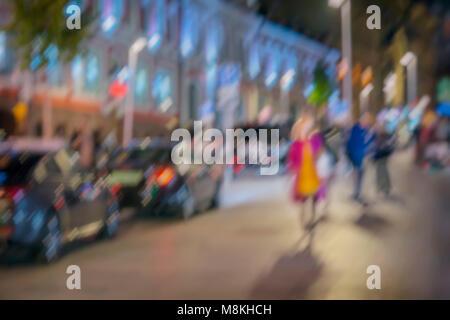 Hintergrund auf Stadt Straße bei Nacht, motion Wirkung. Abstrakte unscharfe Silhouette von Mädchen in hellen Regenmantel - Stockfoto