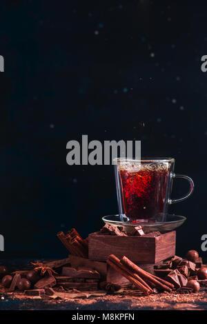 Tee in einem doppelwandigen Schale auf einem Stapel mit Spice Boxes. Zimt, gebrochene Schokolade Stücke, Kakaopulver - Stockfoto