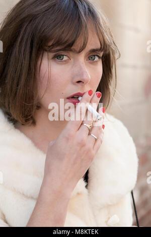 Eine gut gekleidete Frau das Tragen der roten Lippenstift, rauchen eine Zigarette. - Stockfoto