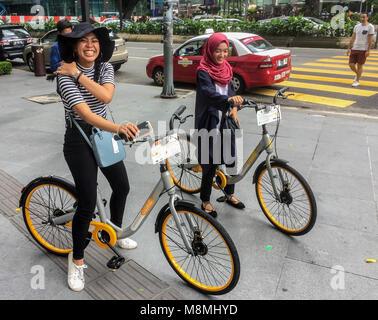 Zwei malaysische Mädchen auf oBikes Fahrräder, Avenue K, Jalan Ampang, KLCC, Kuala Lumpur, Malaysia Stockfoto