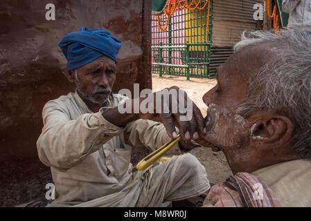 Ein Friseur, ein Mann auf der Straße, Sonepur, Indien zu rasieren. - Stockfoto