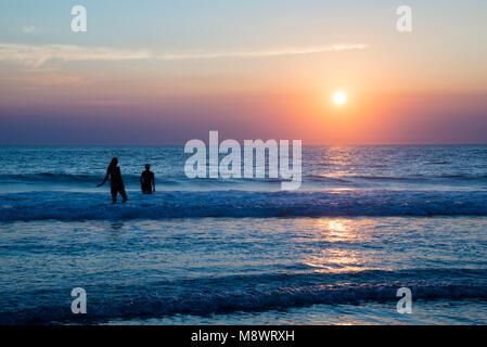Silhouetten von Menschen genießen den Sonnenuntergang am Atlantik, Lacanau, Frankreich - Stockfoto
