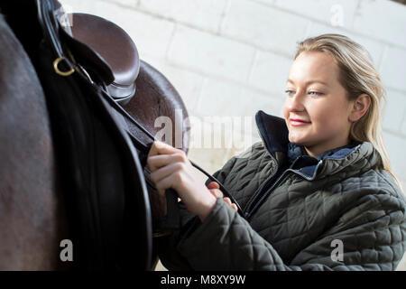 Weibliche Eigentümer einstellen Sattel Gurte in stabilen mit Pferd - Stockfoto