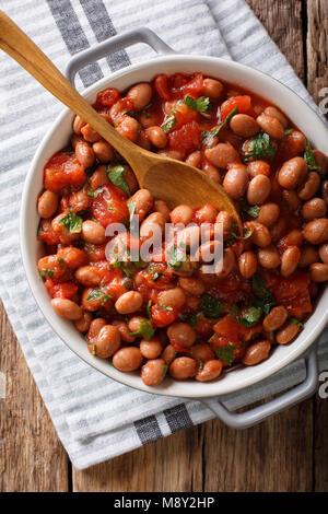 Organische Borlotti Bohnen in Tomatensoße mit Kräutern close-up in einer Schüssel auf den Tisch. Vertikal oben Ansicht - Stockfoto