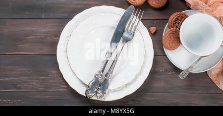 Leere weiße Teller mit Besteck Messer und Gabel, Schale, Krug und Schokolade Cookies auf dunklen Holztisch Hintergrund. - Stockfoto