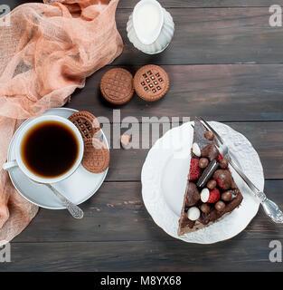 Stück Schokolade Kuchen auf weissen Teller, Tasse schwarzen Kaffee, Kanne und Schokolade Cookies auf dunklen Holztisch - Stockfoto