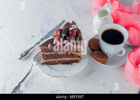 Stück Schokolade Kuchen auf weissen Teller, Tasse schwarzen Kaffee, Kanne und Schokolade Cookies auf weißem Hintergrund. - Stockfoto
