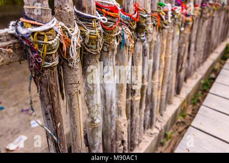 Bunte Armbänder von Besuchern am Aufstellungsort eines Massengrabs links, Choeung Ek Killing Fields Völkermord Center, - Stockfoto