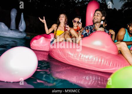 Gruppe Männer und Frauen sitzen auf aufblasbaren pool Matratze. Freunde genießen in einem Pool in Abend. Am Abend Pool Party. - Stockfoto