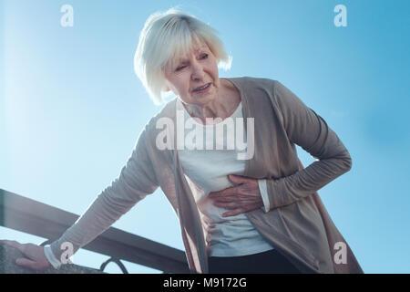 Erschrocken ältere Dame Leiden von Herzinfarkt - Stockfoto