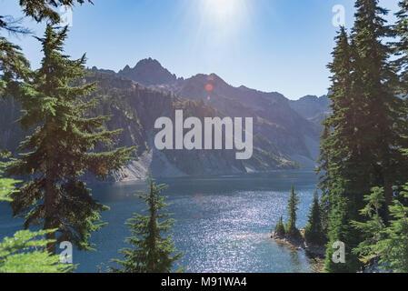 Unberührten alpinen See im Sommer von immergrünen Pinienwald späten Tag Sonnenstrahlen umgeben. - Stockfoto
