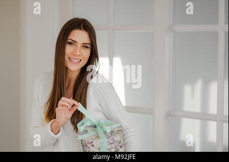 Anspruchsvolle Frau in elegantem Weiß Innenraum home Holding ein wunderschönes Geschenk runden, ziehen Sie das Flachbandkabel und das Öffnen der Verpackung. - Stockfoto
