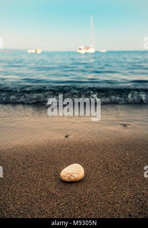 Ein Stein am Sandstrand und Defokussierten Segelboote auf dem Meer - Stockfoto